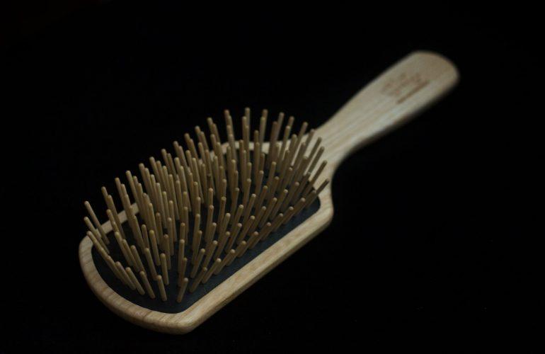 wooden hair brush on black background
