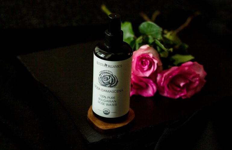 miron glass bottle of alteya organics rose water on dark background with pink roses in the background