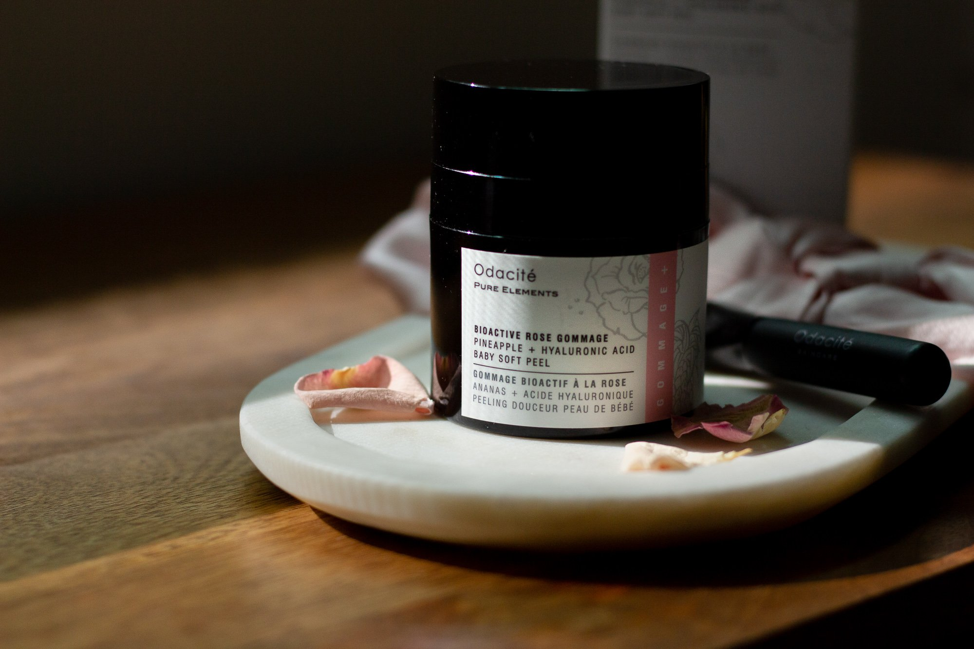 Odacite Bioactive Rose Gommage black jar on marble tray on wooden counter