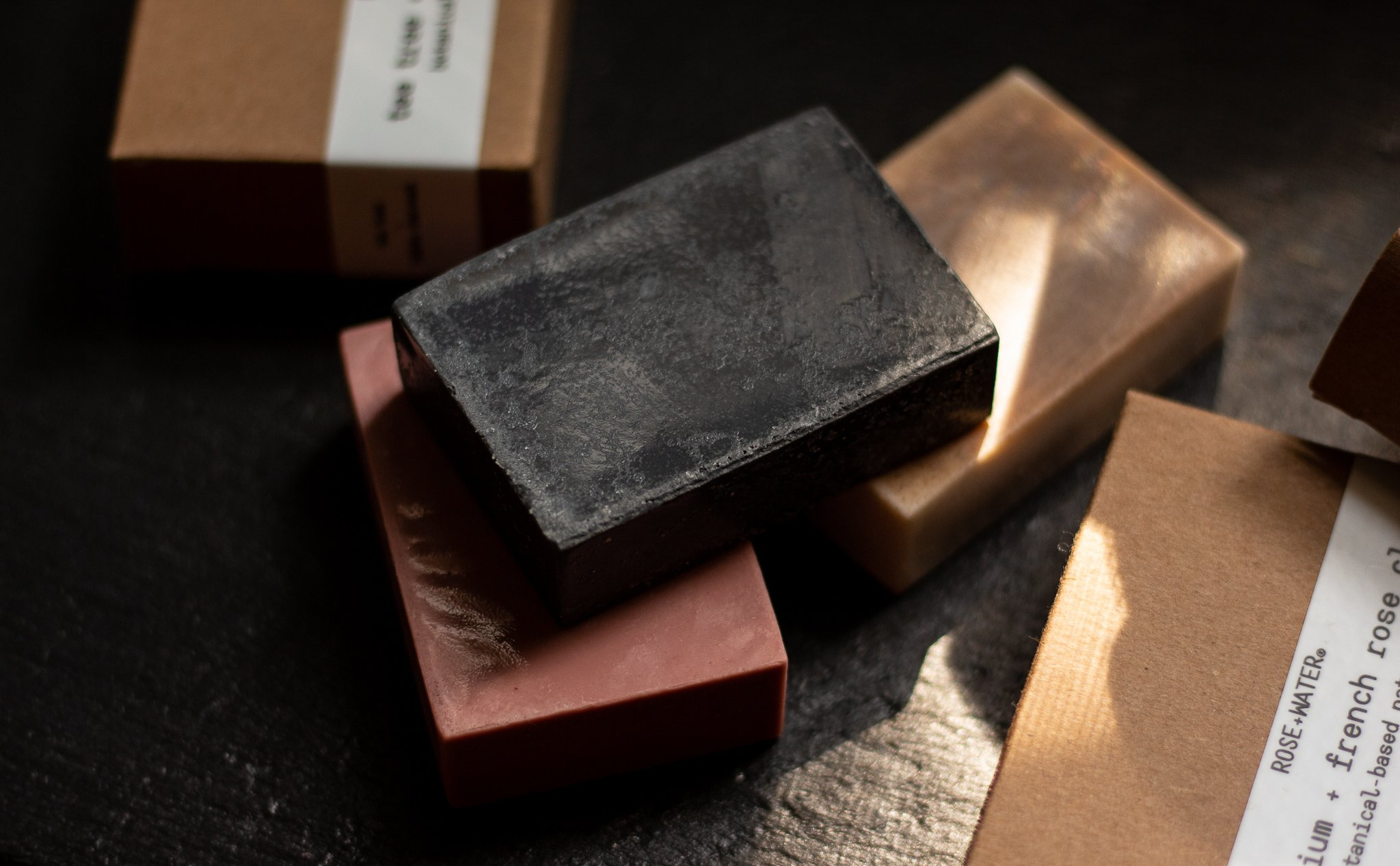 Rose and Water bar soaps piled on top of one another on a slate board